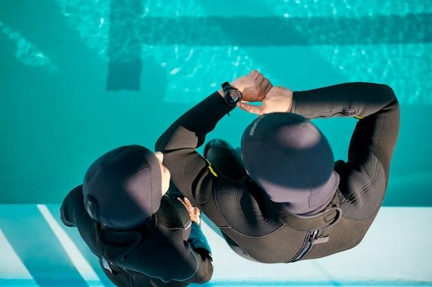Donna e divemaster in attrezzatura subacquea, scuola di immersioni