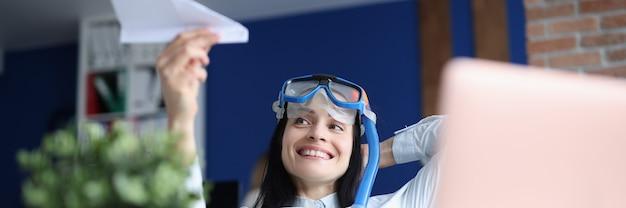 Donna in maschera subacquea che lancia aereo di carta in ufficio