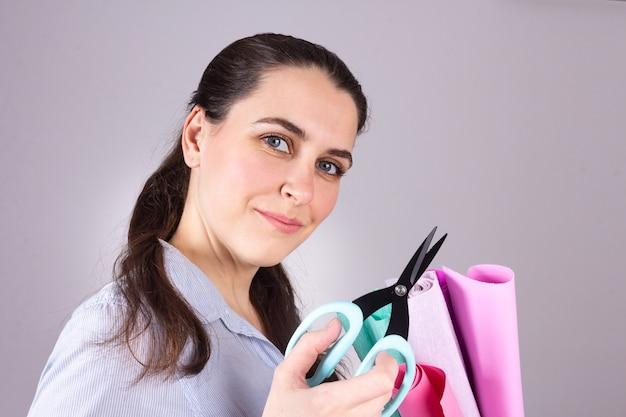 Donna in fai da te tenendo le forbici e rotoli di tessuto. crea un progetto artigianale. scrapbook, cucito, feltro, hobby trapuntato.