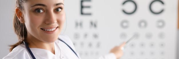 Medico della donna che controlla la vista facendo uso della tavola in clinica