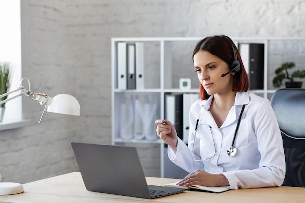 Dottoressa consulta tramite videochiamata assistenza medica in linea.