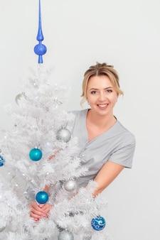 Donna medico o cosmetologo in piedi e sorridente vicino all'albero di natale