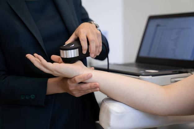 La dottoressa in un abito uniforme scuro sta testando la mano di un paziente per le sue statistiche sulla salute che mostrano sul monitor del laptop