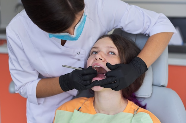 Dentista del medico della donna che cura i denti al paziente della ragazza in studio dentistico