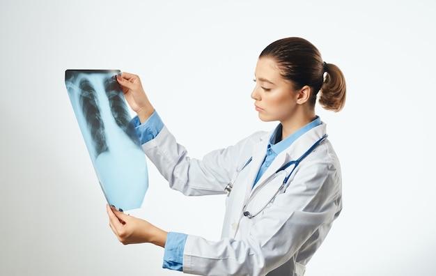 Il medico della donna esamina i vetri dell'abito medico e dei raggi x con lo stetoscopio. foto di alta qualità