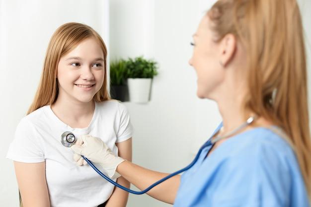 Medico della donna che esamina un ospedale dello stetoscopio del bambino.
