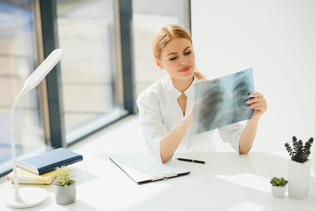 Mani del medico della donna che tengono la pellicola dei raggi x del torace del paziente prima del trattamento