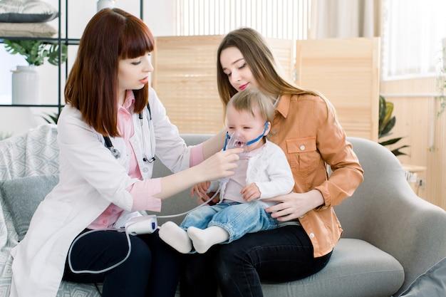 Il medico della donna tiene un inalatore del vapore della maschera per la piccola neonata. trattamento dell'asma. respirare attraverso un nebulizzatore di vapore. concetto di apparecchio per terapia inalatoria.