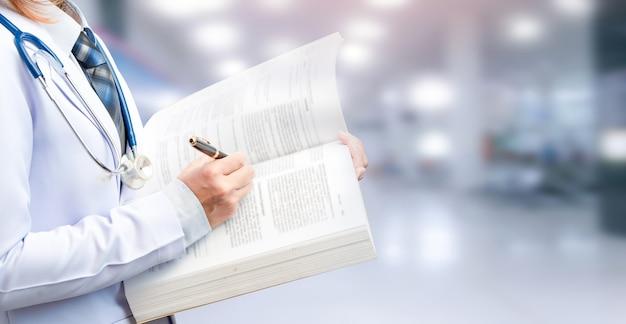 Medico donna che tiene in mano un libro di testo e punta a contenuti importanti su sfondo sfocato