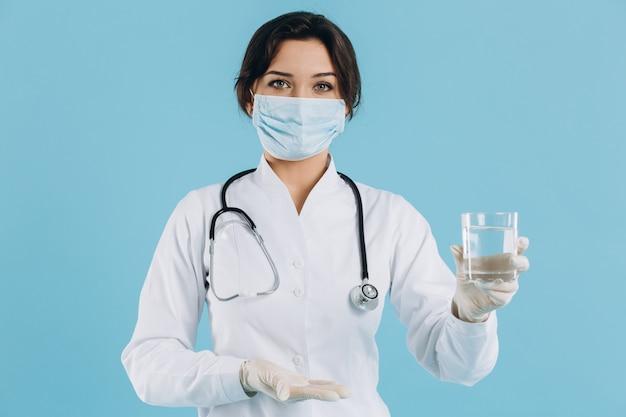 La dottoressa tiene un bicchiere d'acqua e raccomanda di bere acqua per combattere il coronavirus 2019-ncov