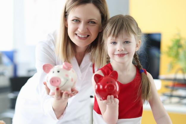 Medico della donna e bambina che tengono i porcellini salvadanaio