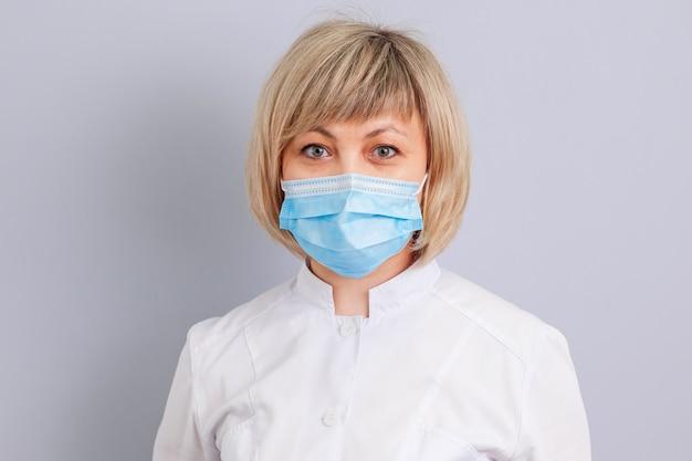 Medico donna in maschera su sfondo grigio