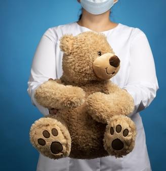 Pediatra medico donna tiene orsacchiotto marrone, concetto di prevenire epidemie e pandemie contro l'influenza