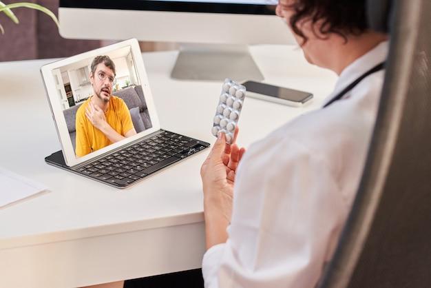 Una dottoressa prescrive pillole a un paziente attraverso una consultazione medica su internet
