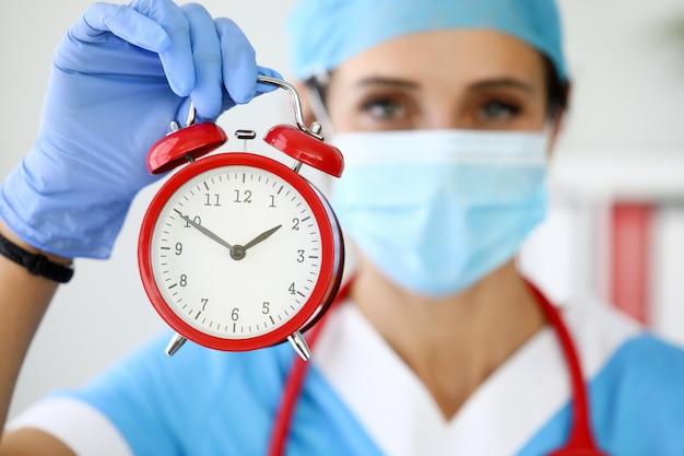Medico della donna nella mascherina medica protettiva che tiene sveglia rossa nelle sue mani