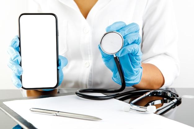 Medico della donna che mostra lo schermo in bianco del telefono cellulare. consulto medico online