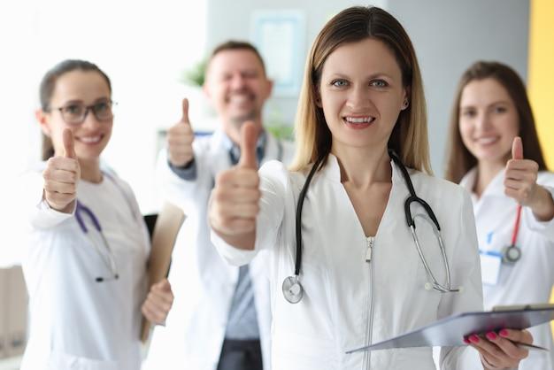 Medico della donna che mostra pollice in su contro i colleghi