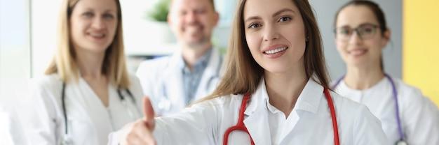 Medico della donna che allunga la sua mano per la stretta di mano sullo sfondo dei colleghi
