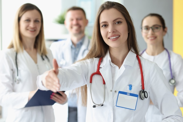 Medico della donna che allunga la sua mano per la stretta di mano con i colleghi