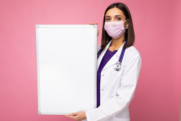 Medico della donna che indossa un camice medico bianco e una maschera che tiene scheda in bianco con lo spazio della copia per testo isolato su priorità bassa. concetto di coronavirus.