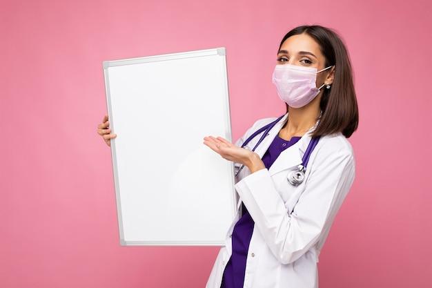 Medico della donna che indossa un camice medico bianco e una maschera che tiene il bordo bianco con lo spazio della copia per testo isolato su fondo. concetto di coronavirus.