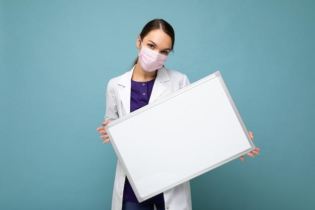 Medico donna che indossa un camice bianco medico e una maschera che tiene un bordo bianco con spazio per la copia per il testo