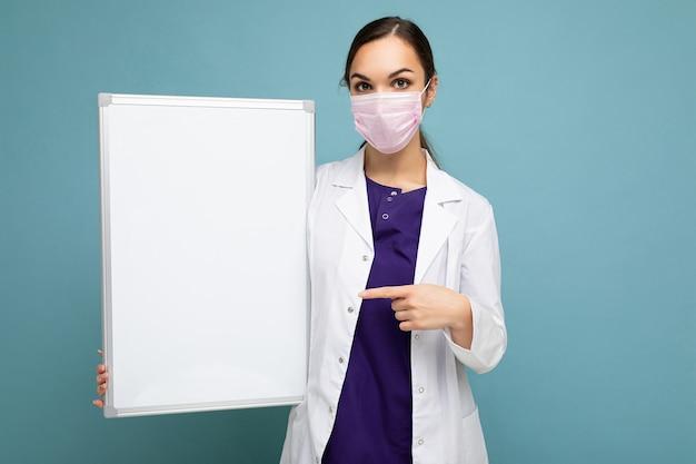 Medico della donna che indossa un camice medico bianco e una maschera che tiene scheda in bianco