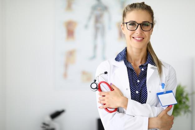 Medico della donna in camice bianco sta con le braccia conserte