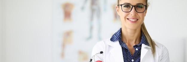 Dottoressa in camice bianco sta con le braccia conserte.