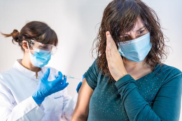 Una dottoressa con maschera facciale che applica il vaccino contro il coronavirus, la paziente con paura del vaccino e dei suoi effetti collaterali.