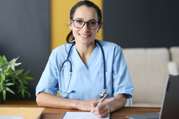 Medico della donna con gli occhiali che compilano la storia medica