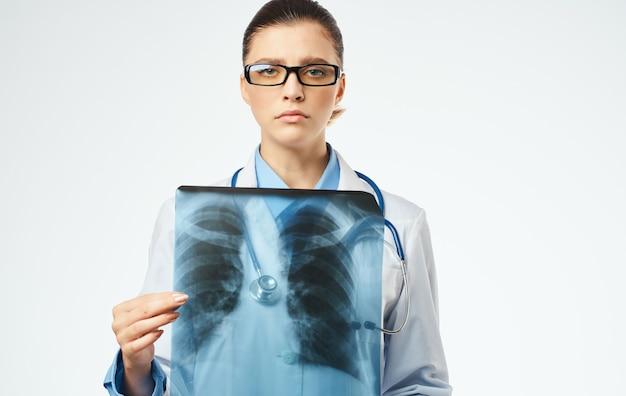 Medico della donna al lavoro con vista ritagliata del primo piano dei raggi x.