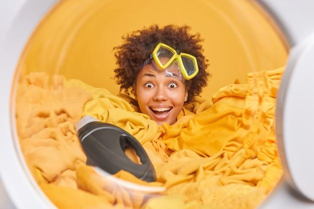 La donna fa il riciclaggio a casa smliles si diverte ampiamente indossa la maschera per lo snorkeling pone in lavatrice il cerchio attacca la testa attraverso il mucchio di biancheria gialla con detersivo