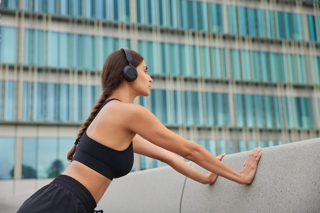 La donna fa esercizi di push up si appoggia su una parete di cemento indossa cuffie stereo ritagliate sulle orecchie ha pose di codino all'esterno si allena all'aria aperta