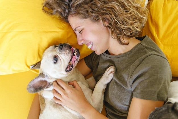 Amante dei cani donna con bulldog a letto. vista dall'alto della donna che gioca con l'animale domestico. stile di vita con animali in casa.