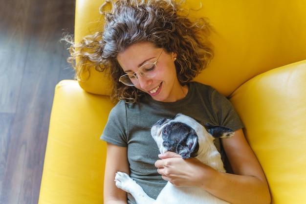Amante dei cani donna con bulldog a casa sul divano. vista dall'alto orizzontale della donna che gioca con l'animale domestico