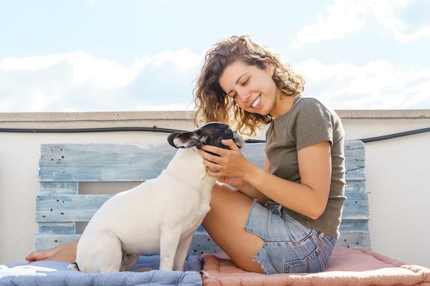Amante dei cani donna con bulldog a casa sul divano. vista orizzontale della donna che gioca con l'animale domestico all'aperto