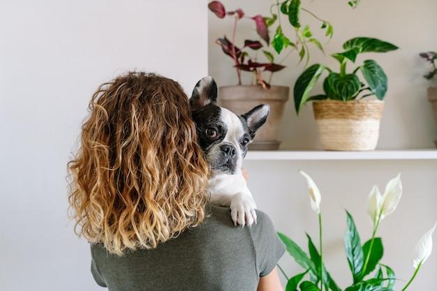 Amante dei cani donna con bulldog a casa. vista posteriore orizzontale della donna che tiene e abbraccia il suo cane con decorazioni vegetali