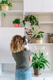 Amante dei cani donna con bulldog a casa. vista posteriore verticale della donna che tiene il suo cane con decorazioni vegetali