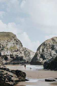 Donna e cane in piedi tra due rocce in spiaggia