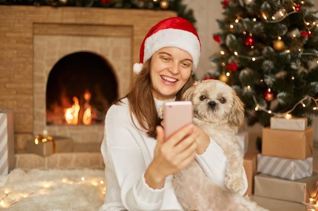 Donna e cane in maglione divertendosi prende il ritratto di un selfie sullo smart phone o ha una videochiamata con qualcuno, si gode il periodo natalizio a casa, indossa il cappello di babbo natale, posa in un salotto festivo.
