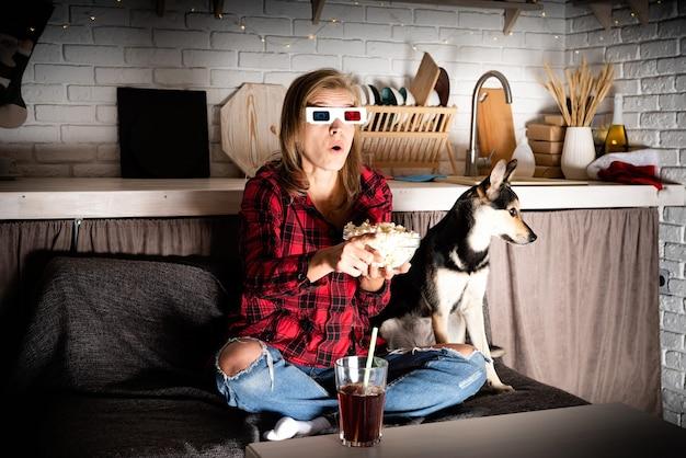 Donna e cane che guardano film a casa