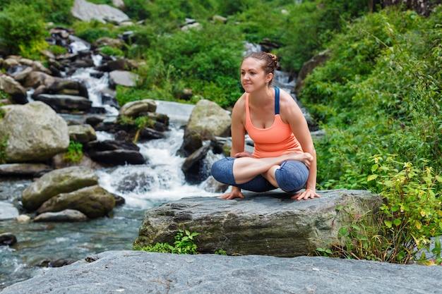 Donna che fa asana tolasana dell'equilibrio del braccio di ashtanga vinyasa yoga