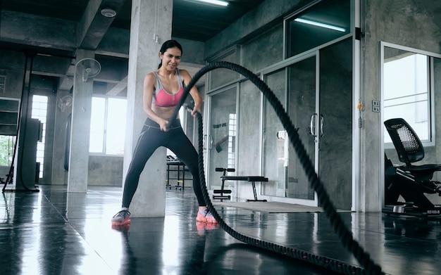 Donna che fa allenamento con la corda di battaglia in palestra