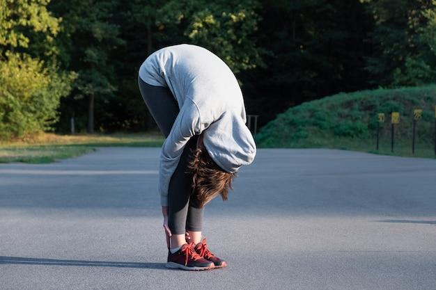 Donna che fa esercizio di yoga per principianti per lo stretching al parco. persona di sesso femminile che allunga prima di fare jogging all'aperto
