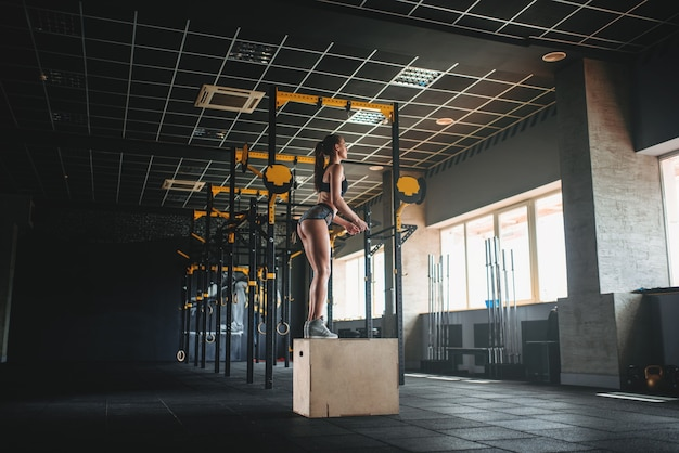 Donna che fa esercizio di salto della casella nel fitness club