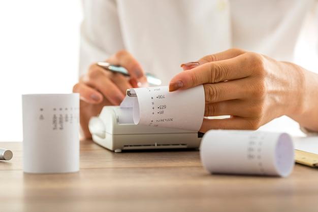 Donna che fa calcoli su una macchina addizionatrice o calcolatrice tirando fuori risme di carta con cifre stampate e totali, concettuale della contabilità di una contabilità, primo piano delle sue mani.