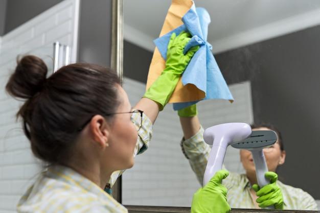 Donna che fa la pulizia in bagno usando l'aspirapolvere, senza l'uso di prodotti chimici domestici. primo piano delle mani guantate con vapore nello specchio, pulizia ecologica