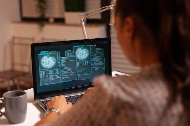 Donna che fa attività criminale nel cyberspazio hackerando il firewall utilizzando il laptop dall'ufficio di casa di notte...