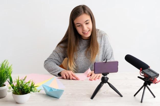 Donna che fa un tutorial di origami sul blog con carte colorate che guarda la telecamera condividendole sui social network in diretta tramite internet online